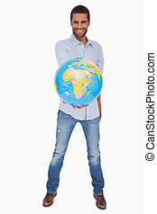 Happy man holding out a globe on white background