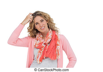 Woman posing and smiling while scratching her head on white...
