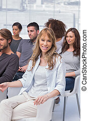 Woman smiling at camera in group therapy all sitting on...