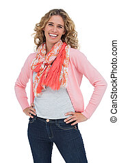 Smiling blonde woman posing with hands on hips on white...