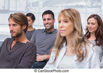 Patients listening in group therapy with one man smiling at...