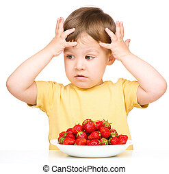 Little boy refuses to eat strawberries
