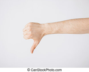 man showing thumbs down - close up of man hand showing...