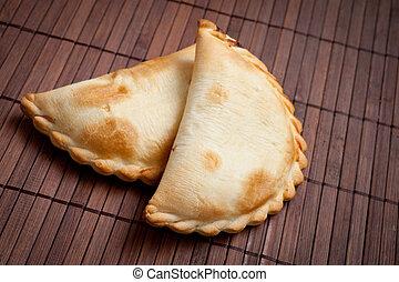 two empanadas. - traditional Argentinian empanadas, or meat...