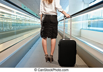 businesswoman with a suitcase on the airport travelator