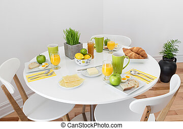Round table with tasty breakfast - White round table with...