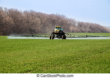 Agricultural machinery spraying the crops with pesticides in...