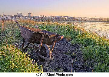 A rusty wheelbarrow abondon with the city in the background