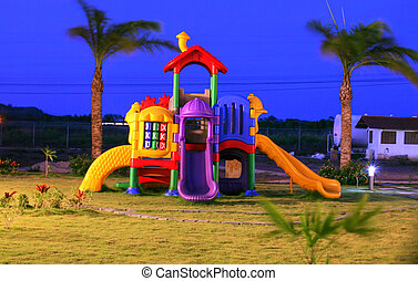 Colorful playground for childrens in the sunset. Focus on...
