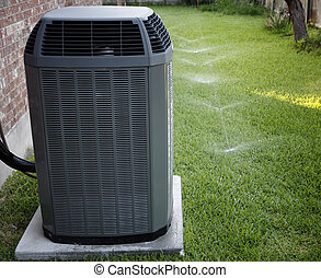 AC and sprinklers - Air conditioner on backyard with working...