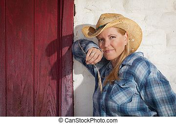 Beautiful Cowgirl Against Old Wall and Red Door