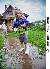 Funny 2 years old baby with father girl playing in puddle -...