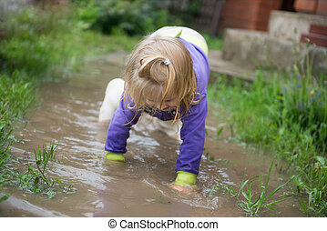 Funny 2 years old baby girl playing in puddle - Happy and...