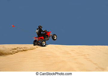 ATV Rider Pulling a Wheelie on a Sand Dune