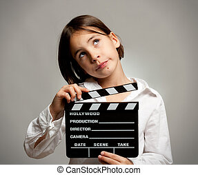 girl with movie clapper board - little girl holding a movie...