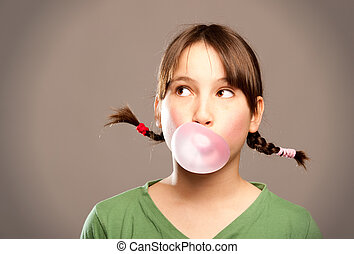 bubble with chewing gum - young girl making a bubble from a...