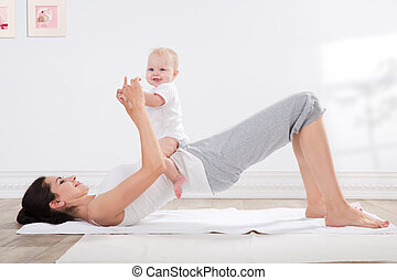 mother and baby gymnastics - young mother does physical...
