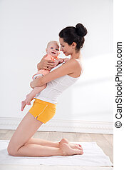 Mother and baby doing exercise - young mother does physical...