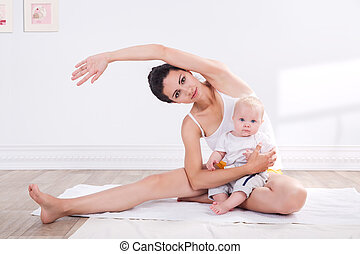 Healthy mother and baby making gymnastics - young mother...