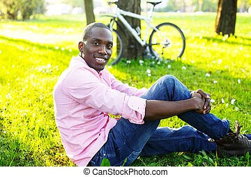 Young happy smiling african american wearing pink shirt with bicycle behind him in a park
