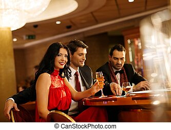 Young people in evening dress behind poker table in a casino