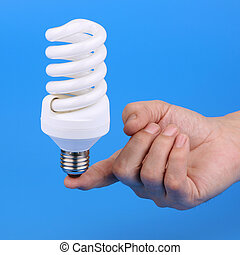 Luminescent bulb and mans hand on a blue background