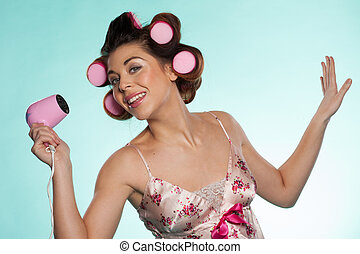 Woman in haircurlers with hairdryer - Fun portrait of an...