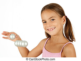 young girl holding a pendulum ball isolated on white...