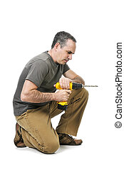 Handyman with a drill - Kneeling handyman pushing on his...