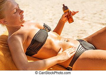 Sensous slim woman applying suntan oil - Sensous slim woman...