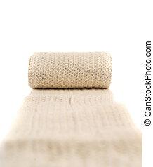 Elastic ACE compression bandage warp unwrapped over white...