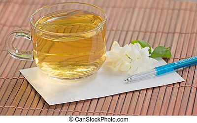 Cup of jasmine tea and paper on bamboo - Cup of jasmine tea...