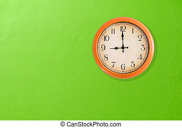 Clock showing 9 oclock on a green wall