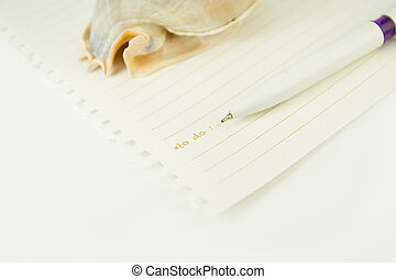 Paper note with pen and seashell paperweight