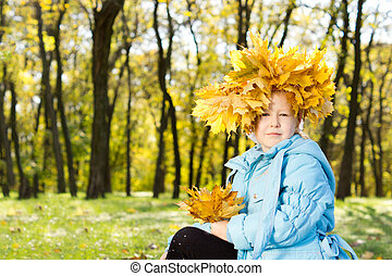 Proud little girl in autumn splendour sitting with a crown...