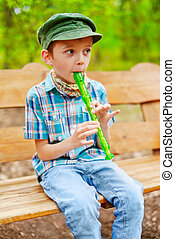 Young kid playing recorder - Young stylish boy plays on...
