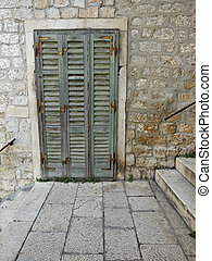 Old green shutter door between stairs in old town Sibenik,...