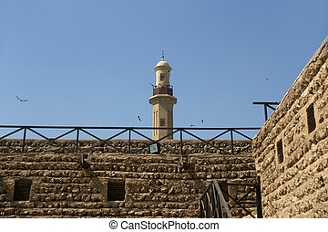 Old Fort and  tower of a nearby mosque. Dubai , United Arab Emir