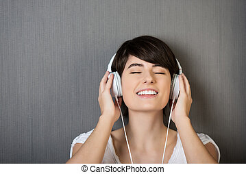 Young woman listening to music - Head and shoulders studio...
