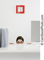 business and work - Young businesswoman hiding behind desk....