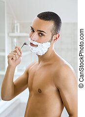 man shaving - Young man shaving indoors and smiling. Copy...