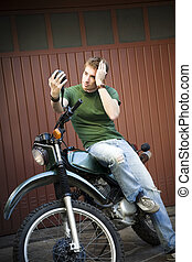 motorbike - Portrait of young man sitting on motorbike and...