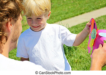 Giving Father a Gift - A cute toddler boy gives his dad a...
