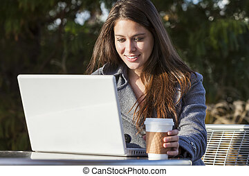 Young Woman Girl Using Laptop Drinking Coffee - A young...