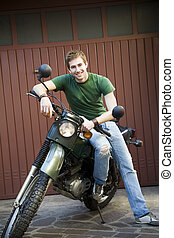 motorbike - Portrait of young man sitting on vintage...