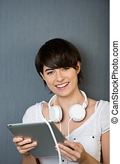 Young woman with a tablet and headphones preparing to listen...