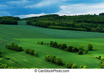 green scenery landscape fields in spring time under clue cloudy sky