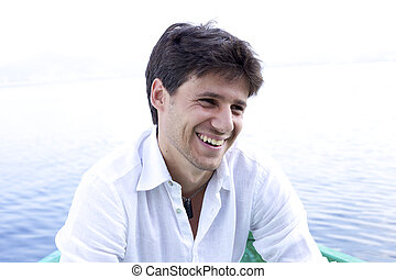 Smiling happy man on boat - Handsome young man happy about...