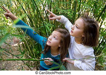 sister twin girls playing in nature pointing finger from...