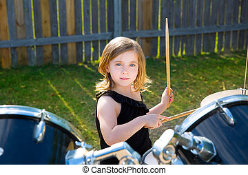Drummer blond kid girl playing drums in tha backyard lawn
